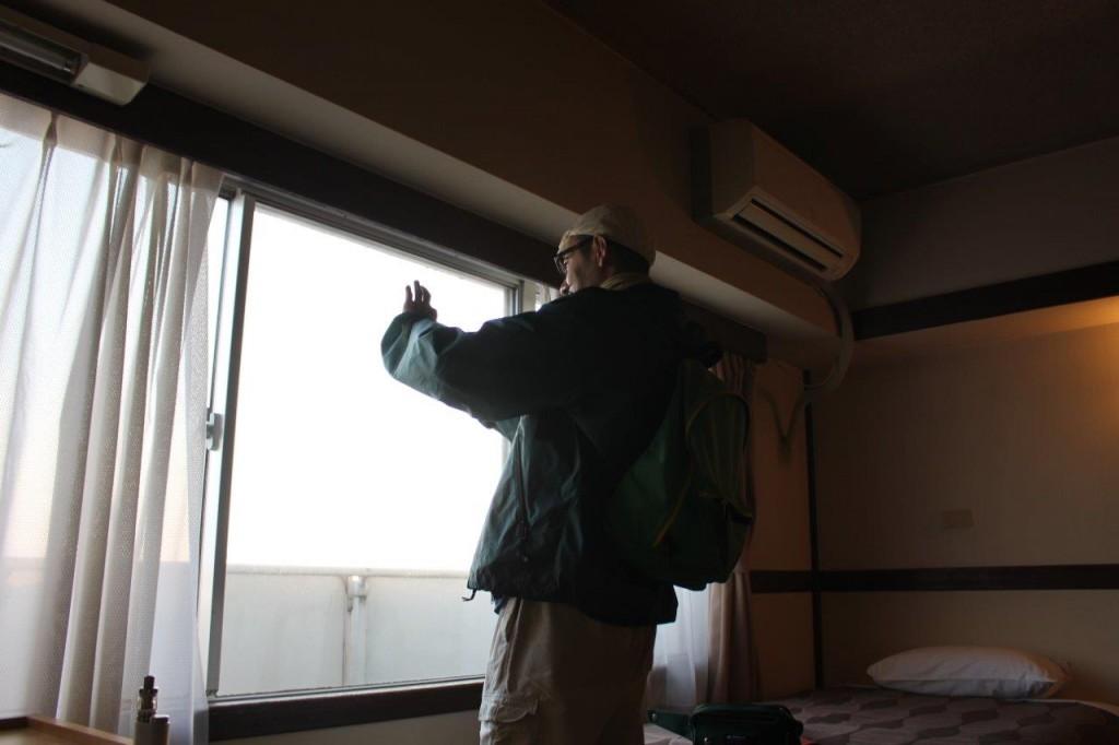 宿は琵琶湖大橋近くのホテル。5時起床。窓からの琵琶湖を撮影する江橋部長。