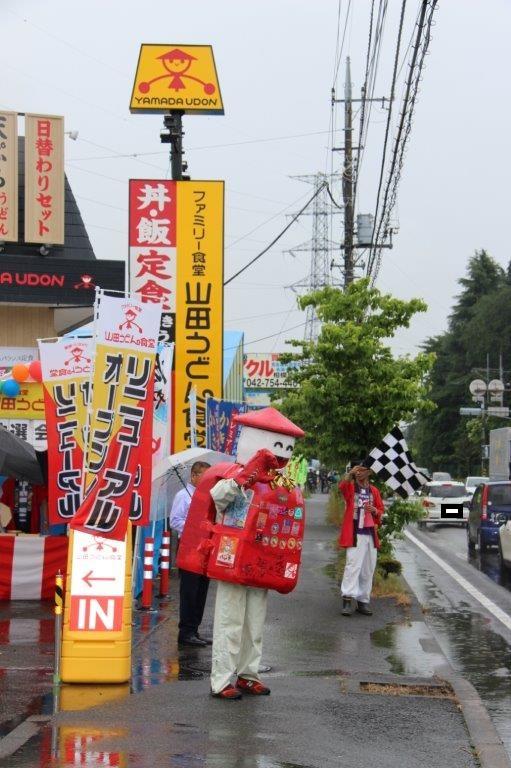 渋滞の車に手を振る案山子くんとチェッカーフラグを振る江橋部長。